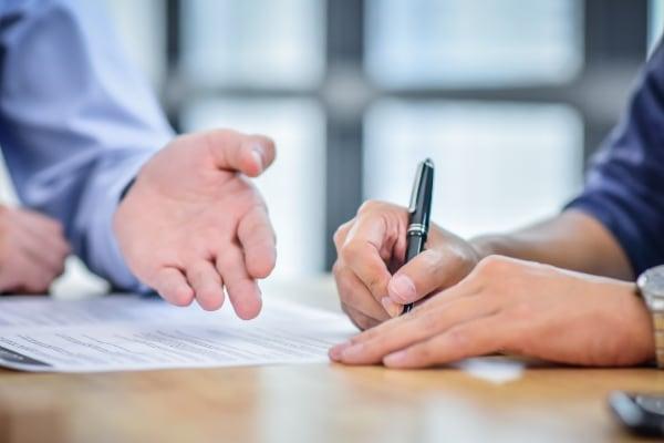 företag möte två män penna kontraktskrivning köpa sälja företag signa